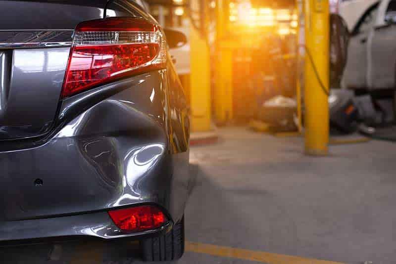 close up fo rear bumper dent in car